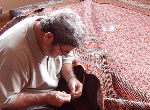 Man sewing the rug